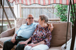elderly couple on swing in backyard