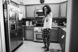 mom stands in kitchen forgetting why she came in there