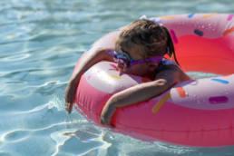 girl swims in donut raft