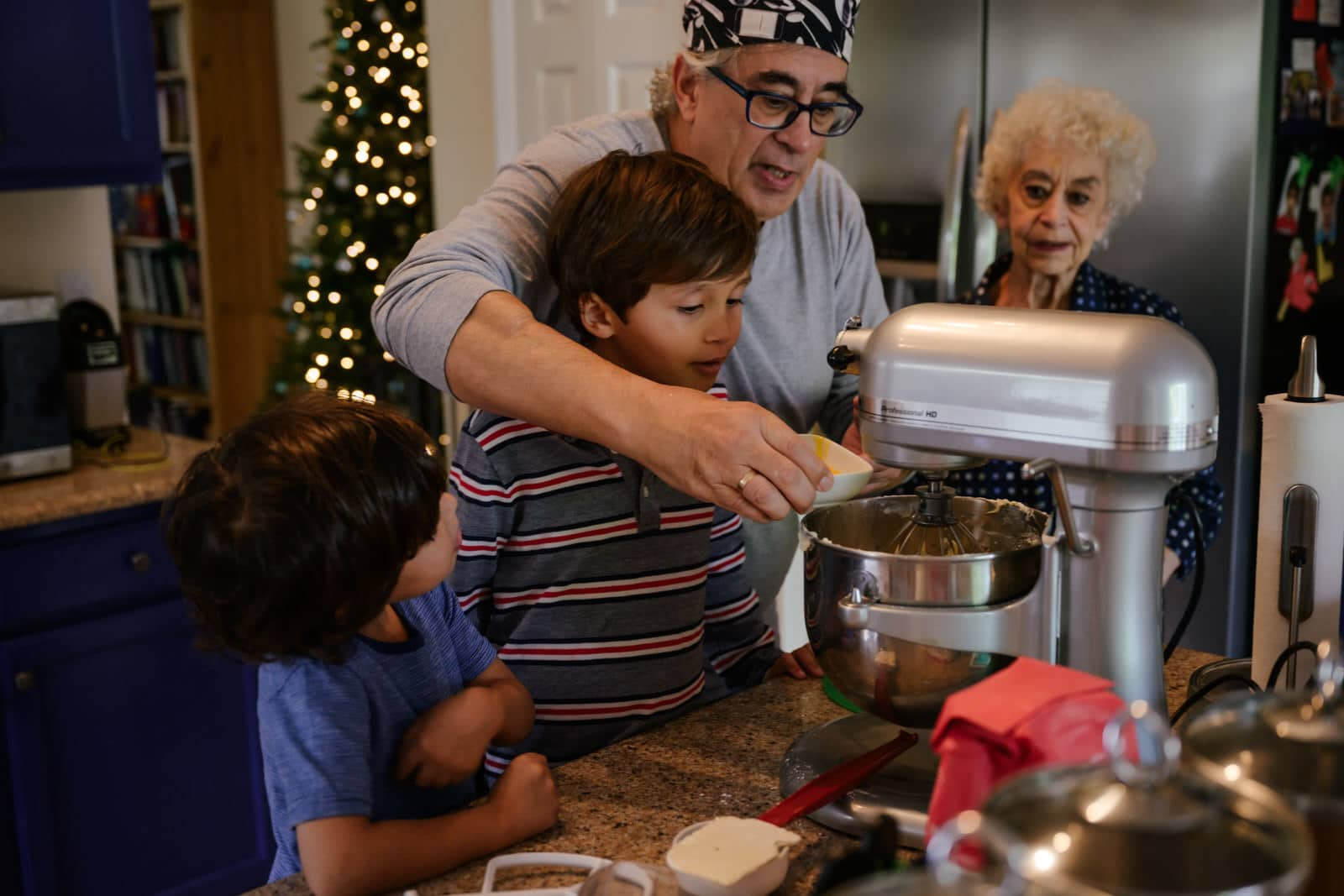 grandfather shows grandsons how to make greek cookies