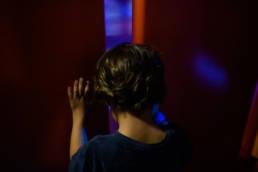 boy pushes open door to the Alien Saucers