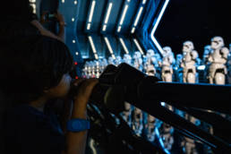 boy looks out at a room full of Stormtroopers