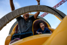boy and dad excitedly ride rollercoaster