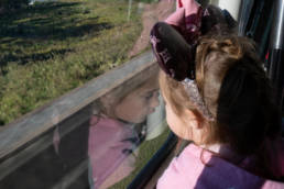 girl looks out at her reflection on the monorail