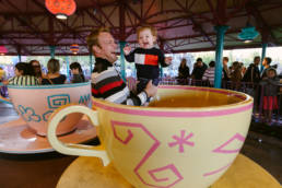 father and daughter play before taking a spin in the teacups