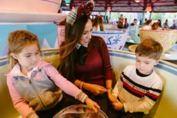 mother takes a spin with the kids in the tea cups
