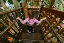 girl climbs down stairs in treehouse