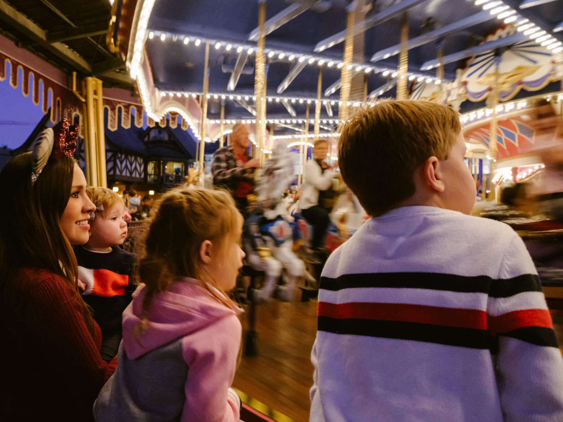 family views the carousel while waiting in line
