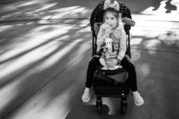 girl sits in stroller and eats popcorn