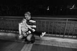 Father comforts tired daughter while waiting for the monorail