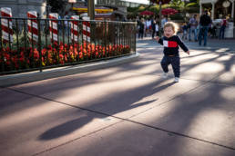 baby chases shadow down Main Street USA