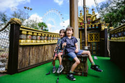 environmental portrait of two boys on a miniature golf course