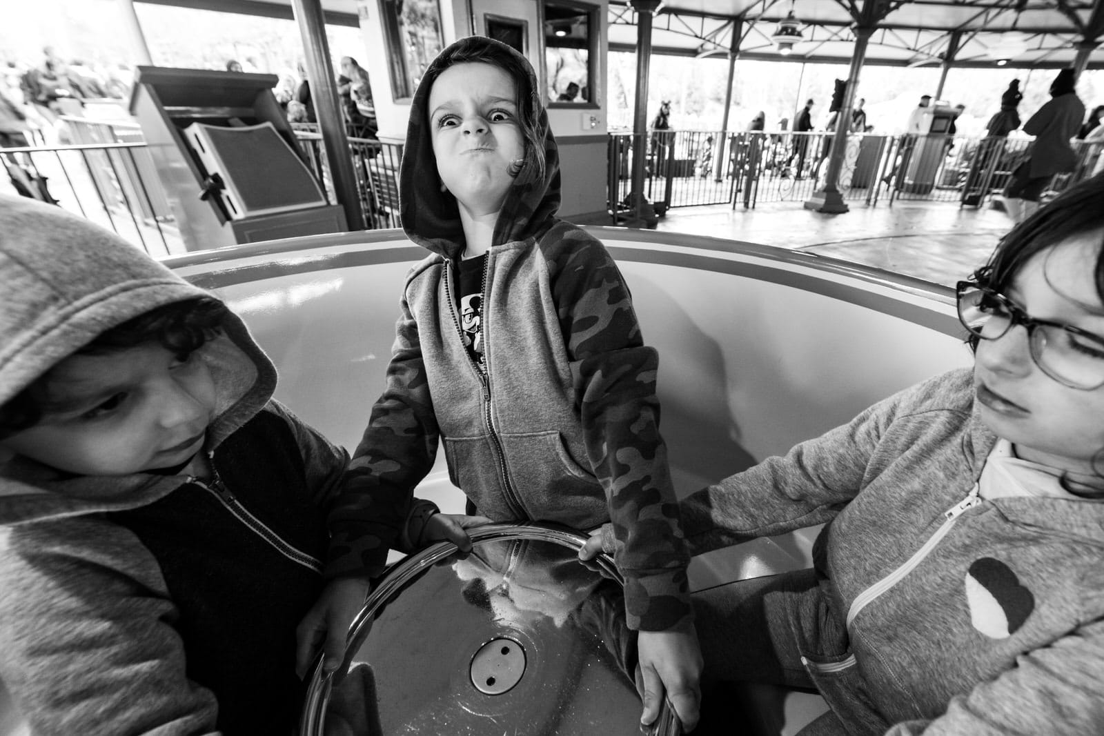 boy tries to lift wheel of the Tea Cups ride