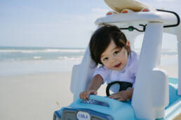 boy climbs around in toy car at the beach