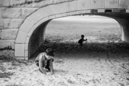 boys play in dirt under a bridge
