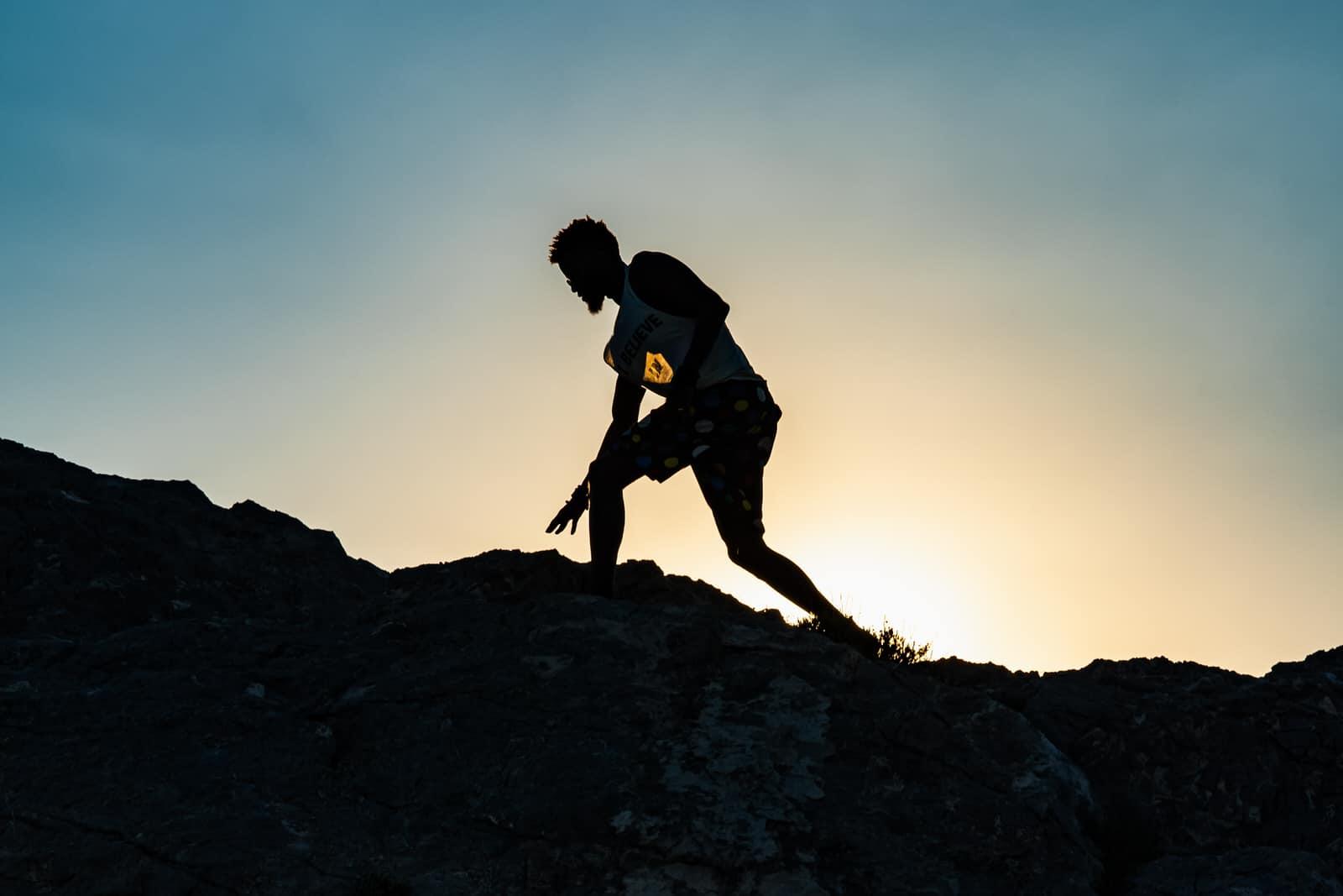 man climbs mountain in silhouette