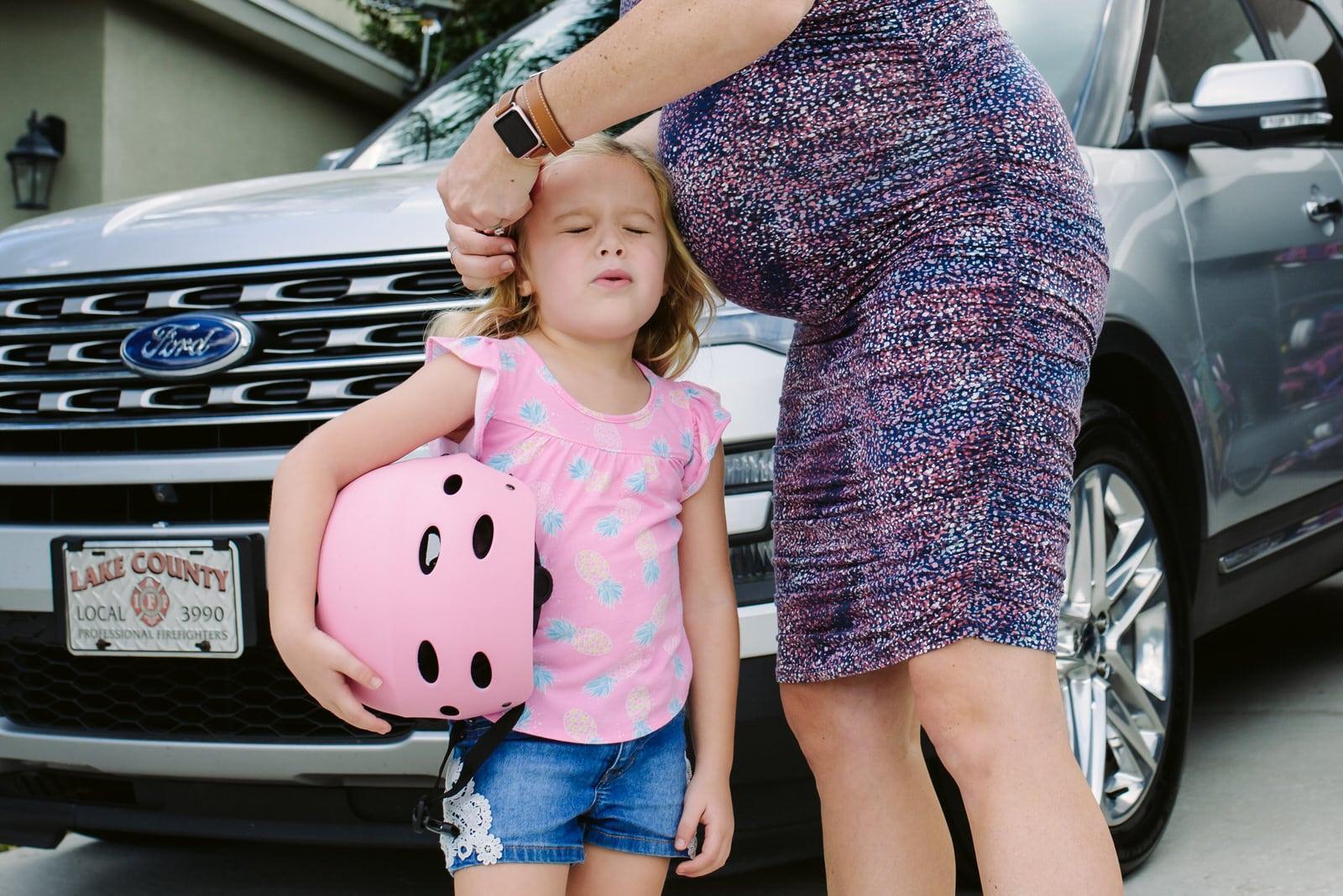 little girl winces as mom fixes hair