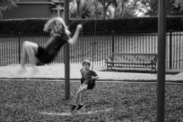 boy watches an older child swing high on the playground