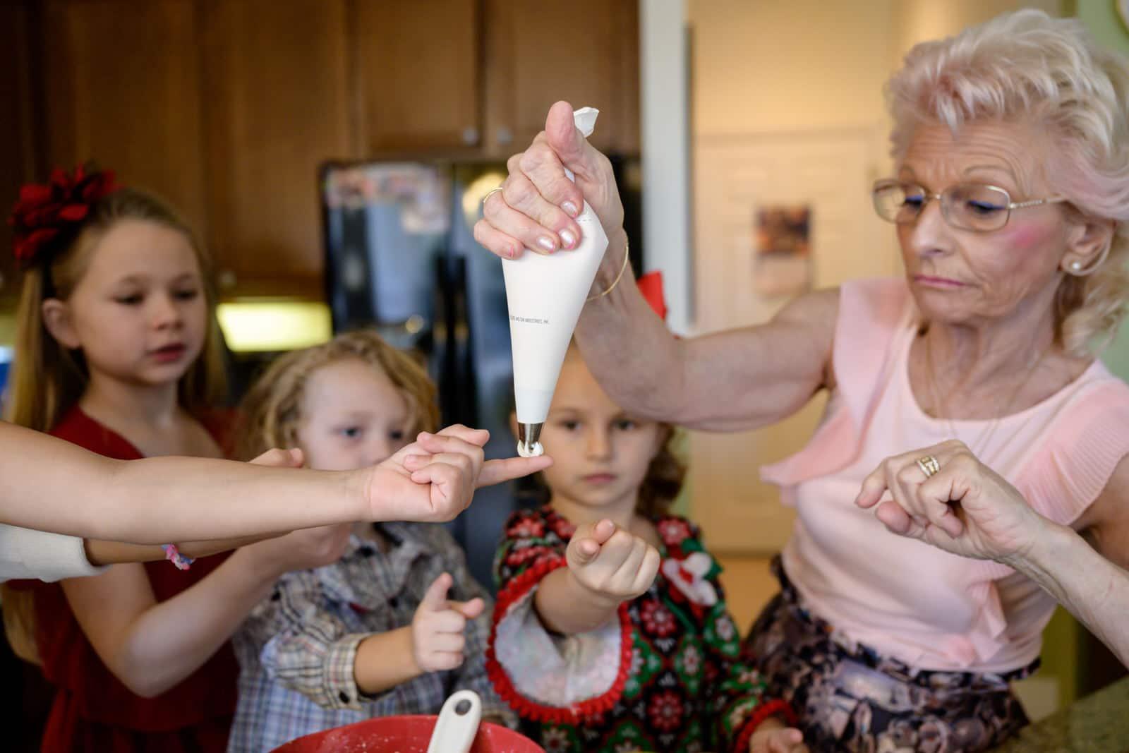 grandma allows kids to taste the frosting during cupcake baking