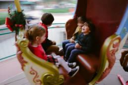 kids enjoy rocking sleigh on carousel