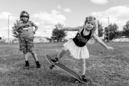 girl on a skateboard while boy looks on