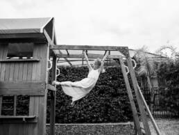 girl on the monkey bars in a dress