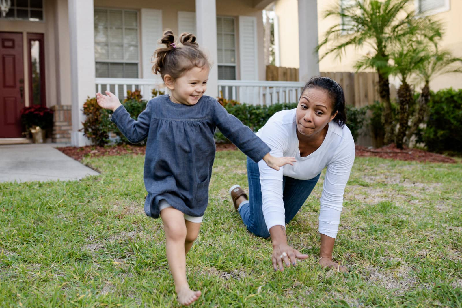 daughter and mom play in front yard