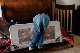 boy hangs over his toddler bed guard