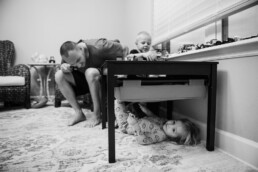 girl hides under her brother's lego table