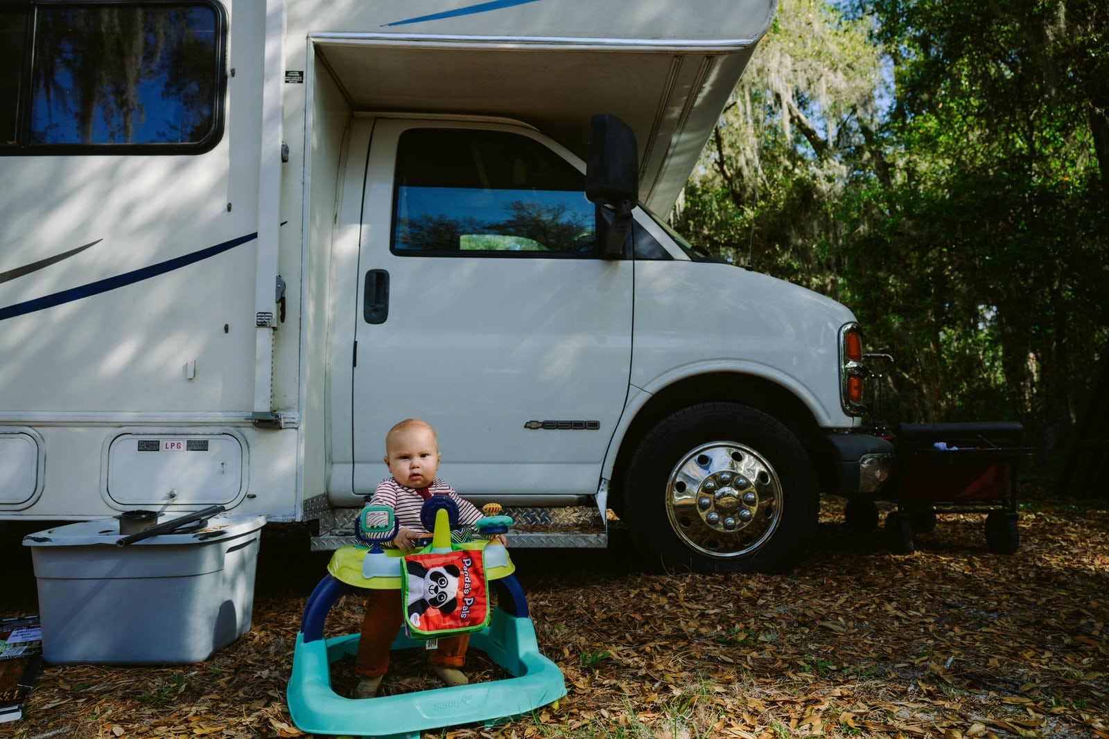 baby sits outside the family camper