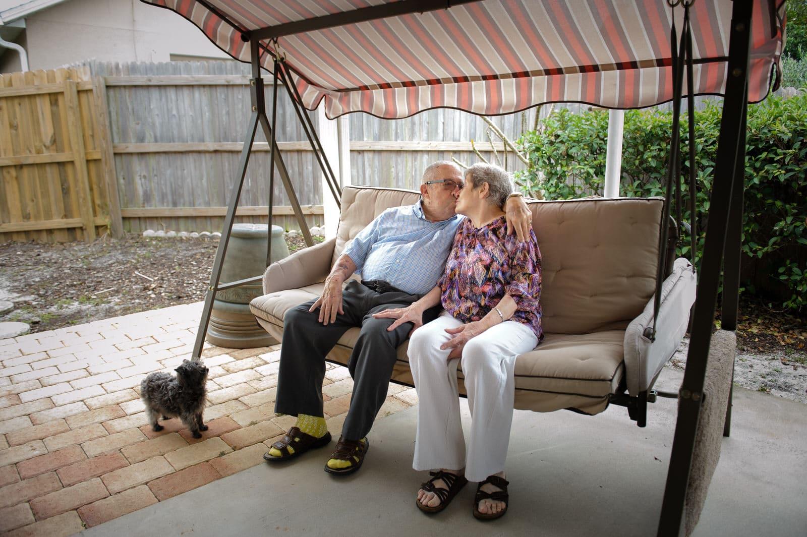 grandma and grandpa share a kiss in the backyard