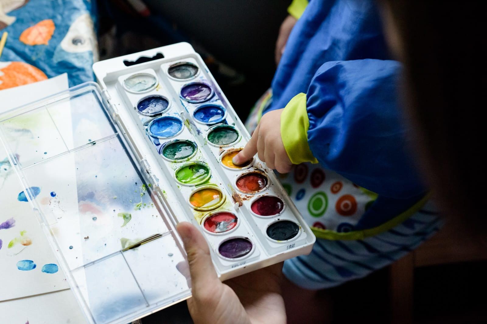 boy paints with fingers