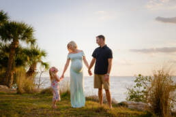 family on the water's edge during maternity session
