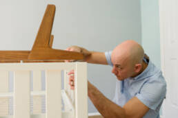 man sets legs in place on pottery barn crib