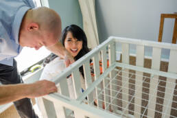 wife laughs at husband building crib