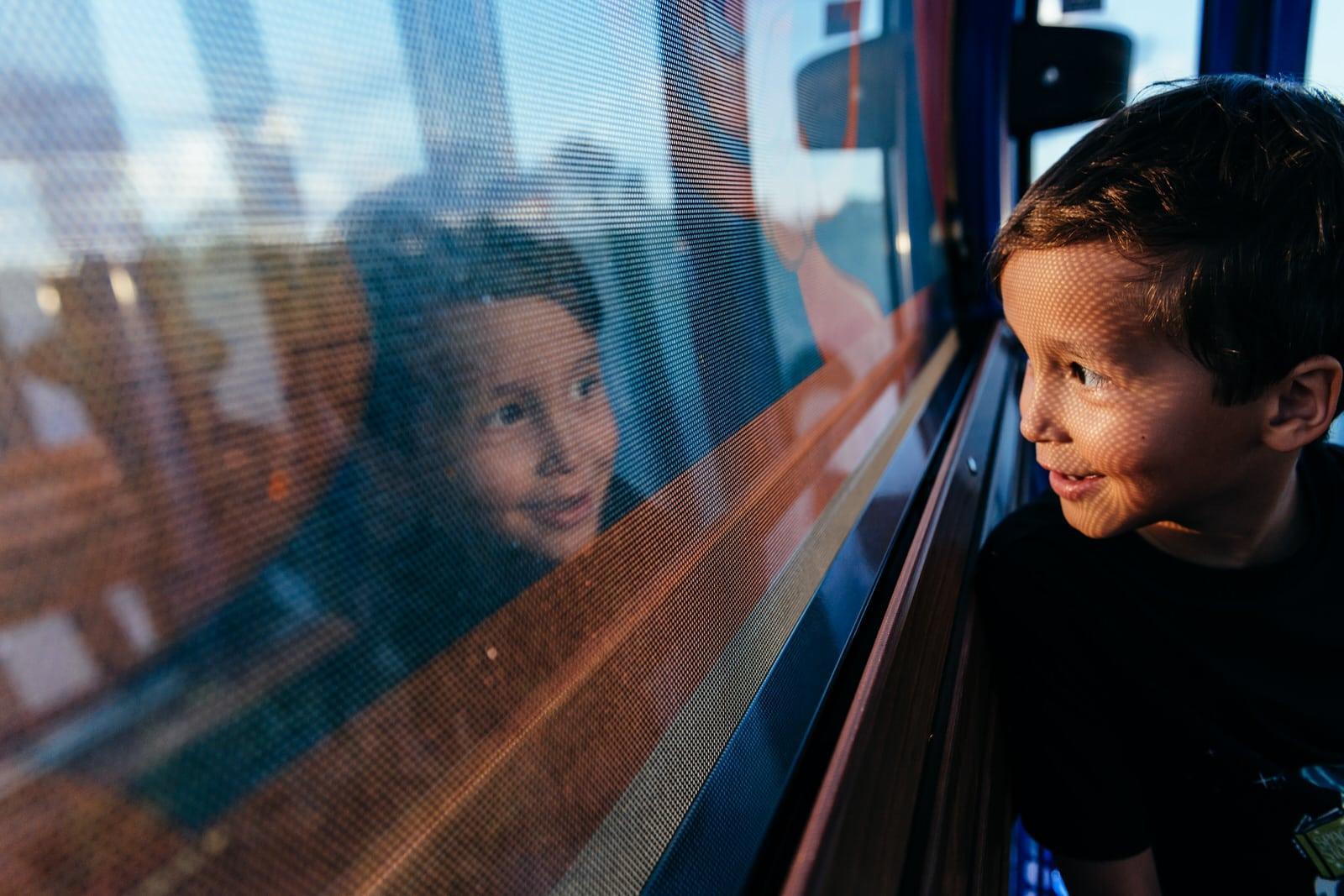 boy looks out window of Disney Skyliner