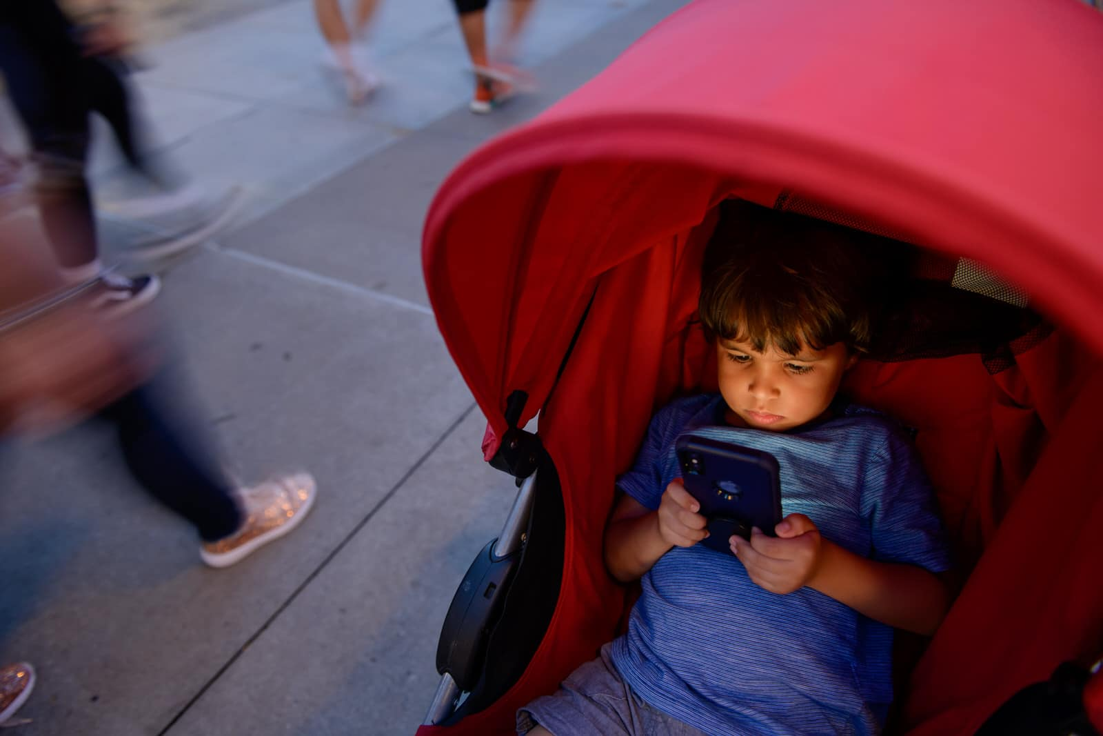 boy watches phone while crowd walks by