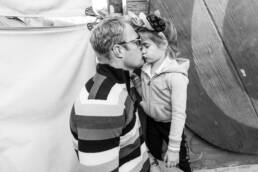 Dad kisses daughter while she pouts