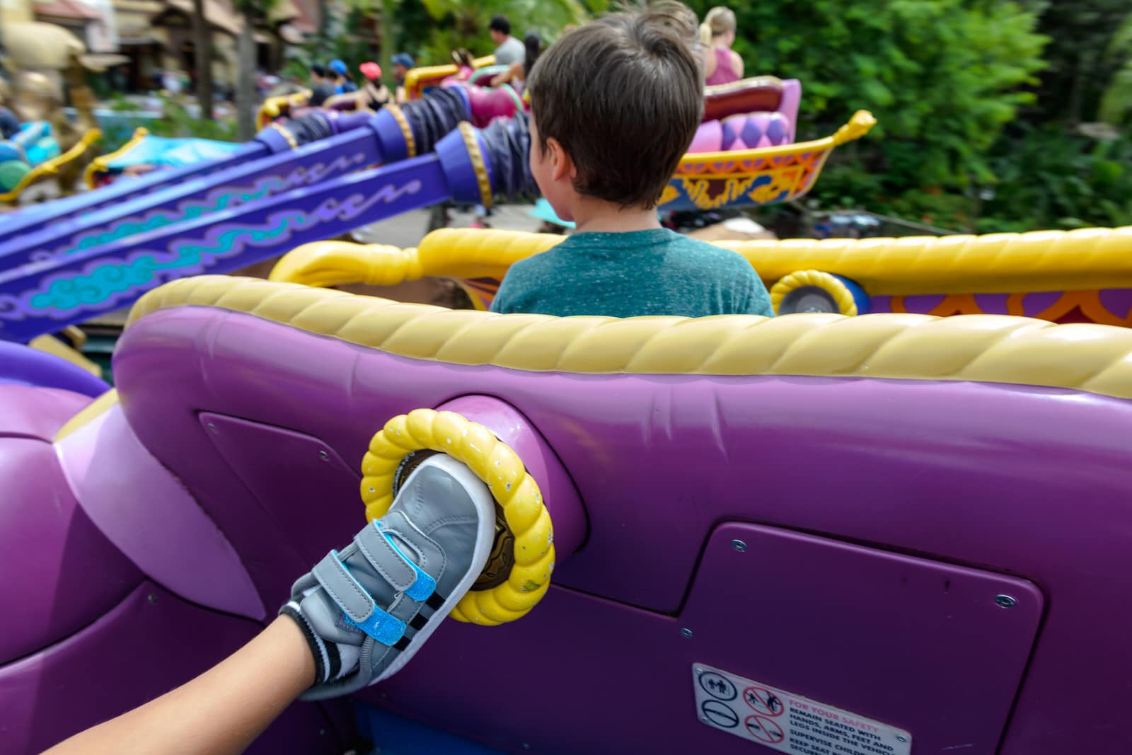 boy presses button with his foot on Magic Carpet ride