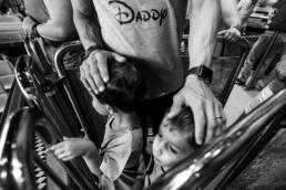 dad calms his boys while waiting in line