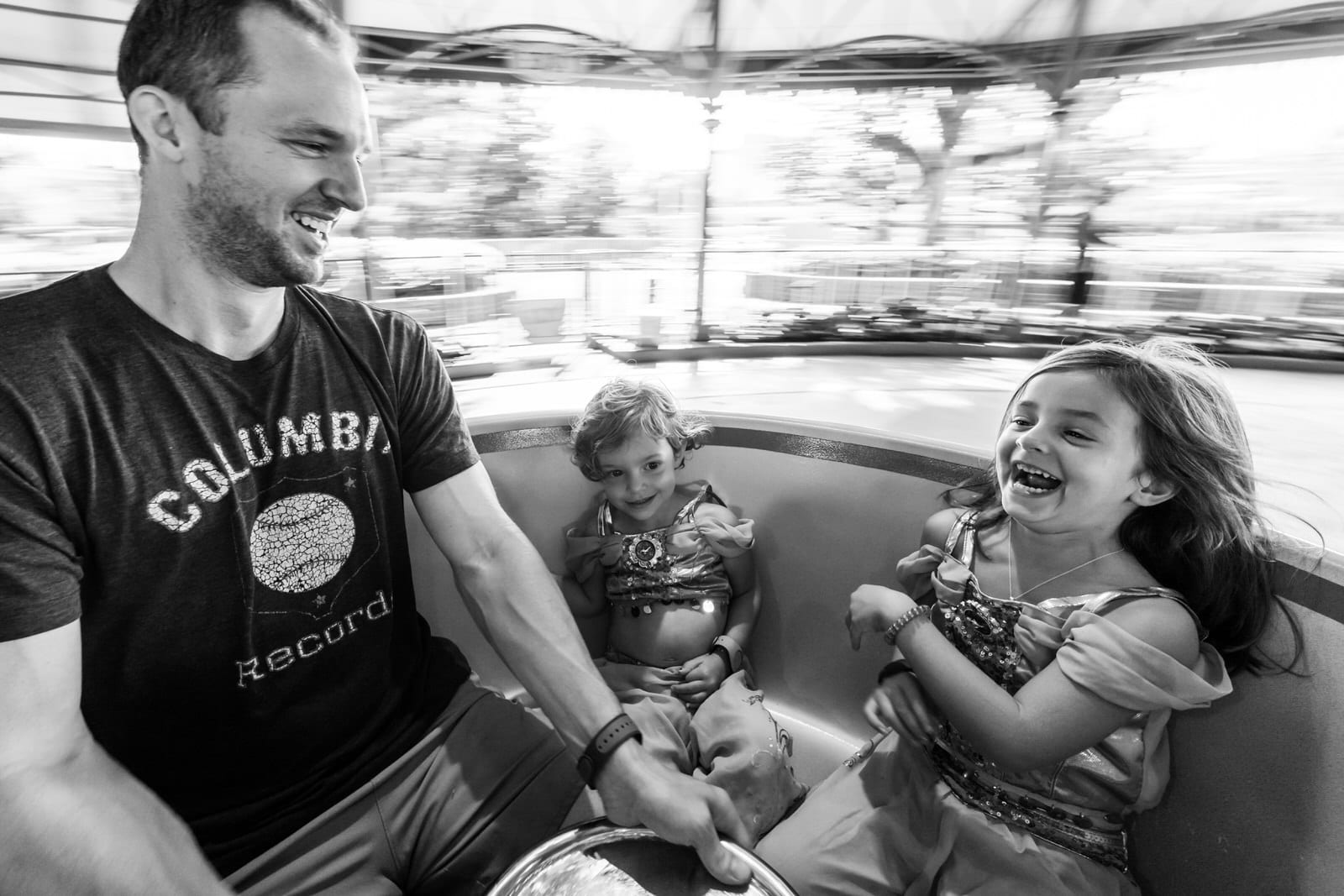 dad spins his daughters fast on the tea cups