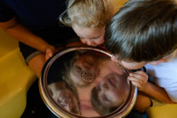 kids look at their reflection on the tea cups ride