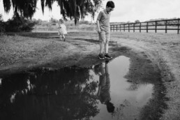 kids play around a puddle between family portraits