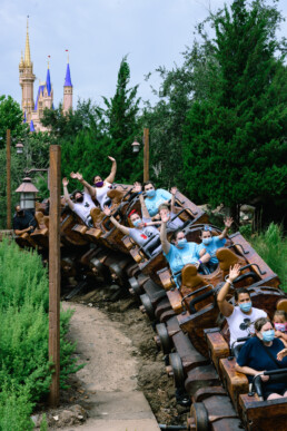 family rides Seven Dwarfs Mine Train with masks on