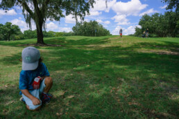 boy rests in shade on hot day at the golf course