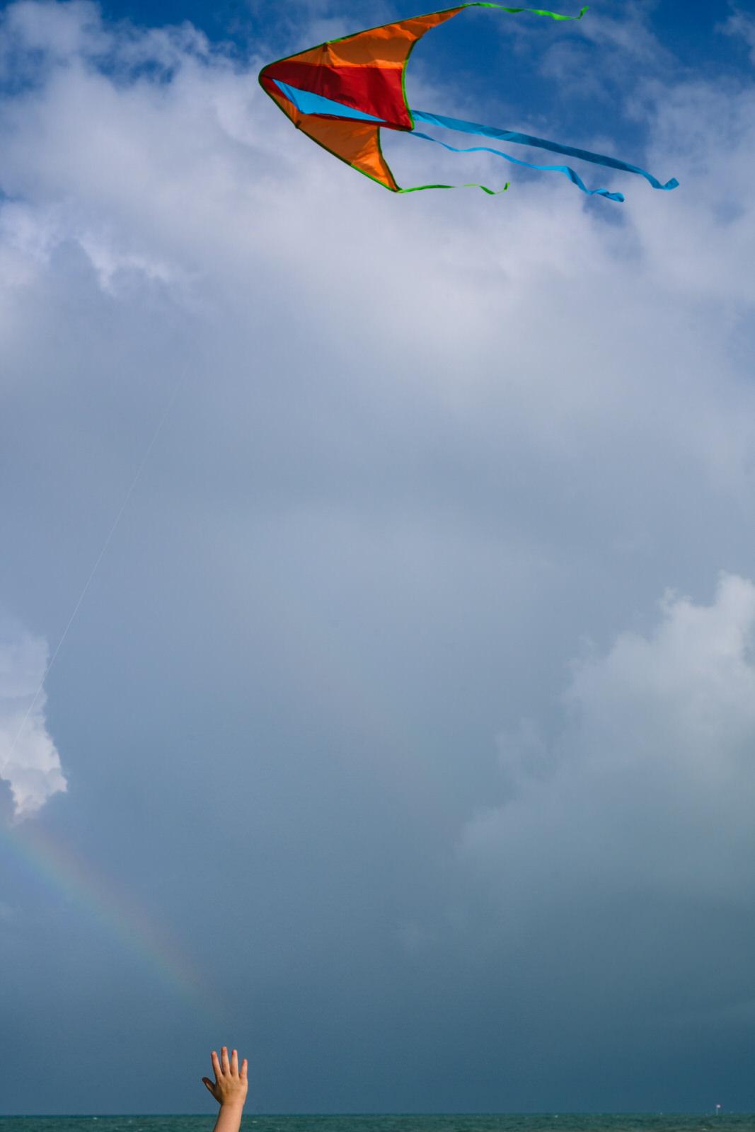 girl reaches for the rainbow as a kite flies overhead