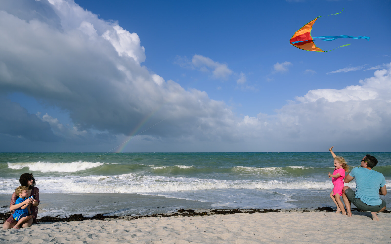 family flies a kite at the beach with a rainbow over the ocean