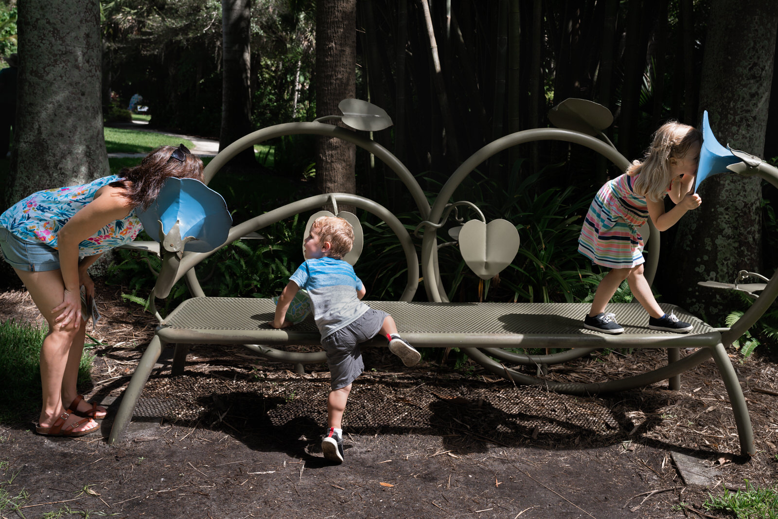 family plays the the whisper bench at McKee Botanical Garden