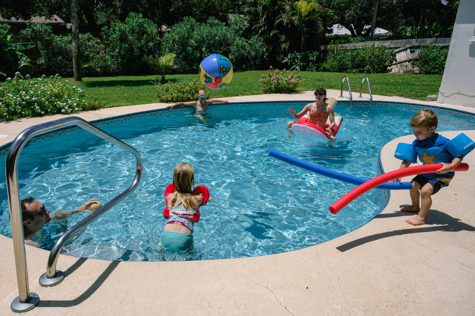 family plays together in the pool