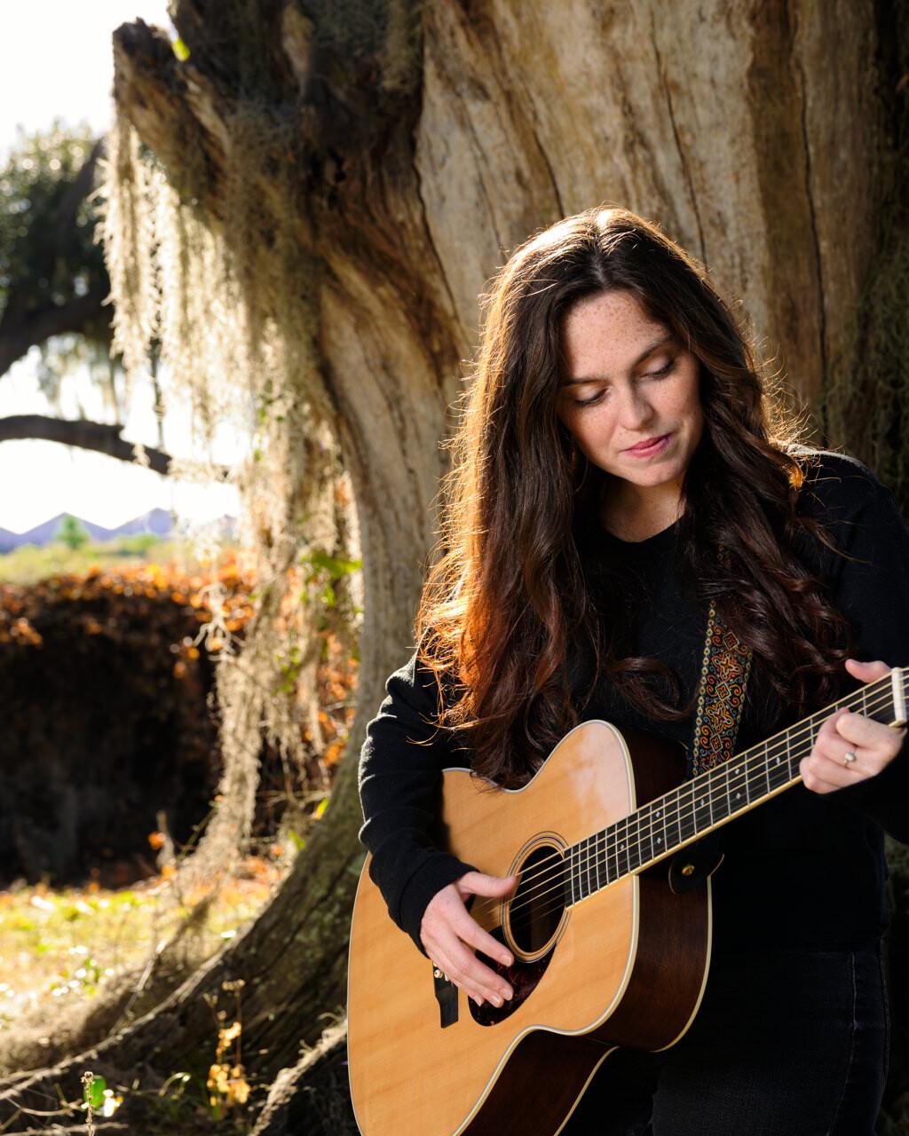 Layla Brisbois singer-songwriter based in orlando strumming her guitar